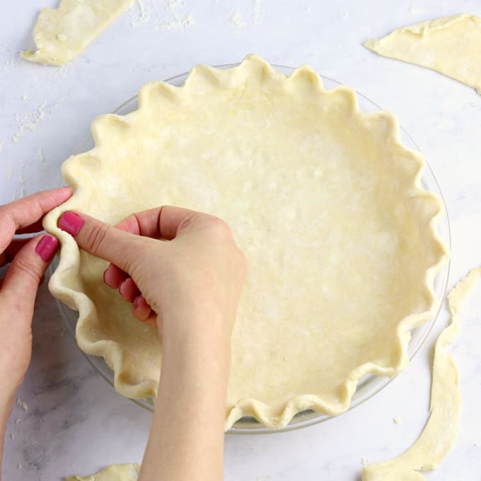Fluting a pie crust with fingers.