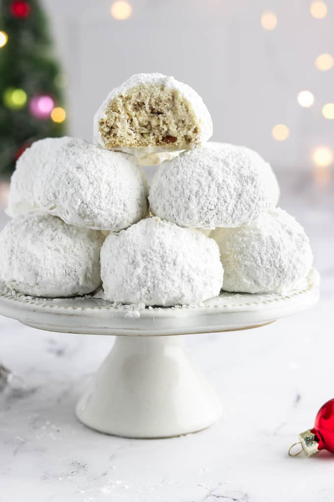 Stack of vegan snowball cookies on a stand with one cookie cut in half.