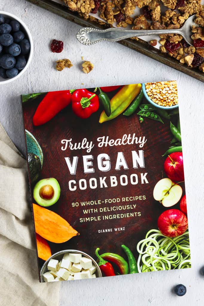 Image of the Truly Healthy Cookbook with napkin, blueberries and granola on the side.