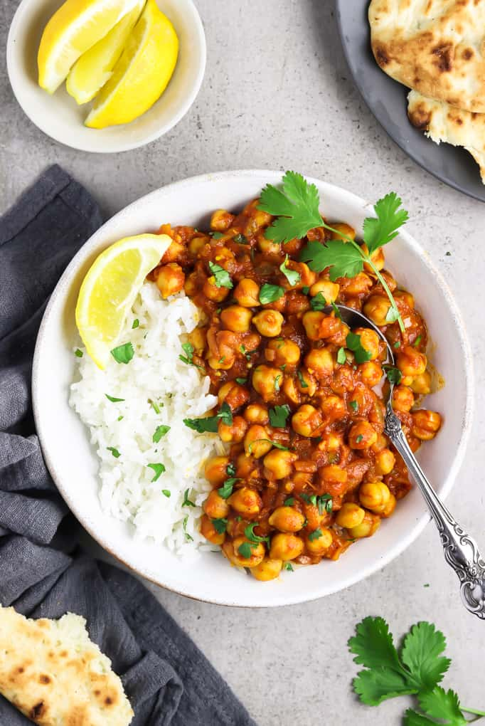 Overhead view of chana masala in a white bowl alongside rice. Garnished with a lemon wedge and cilantro.