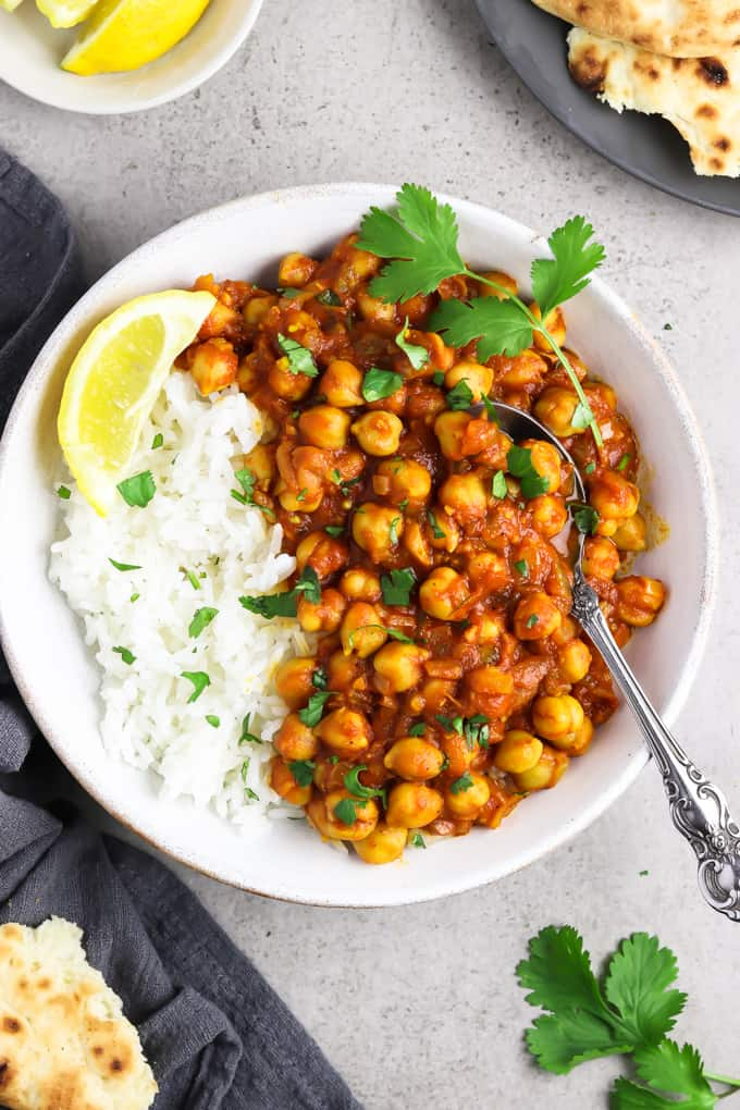 Overhead view of easy chana masala in a white bowl with naan and lemon on the side.