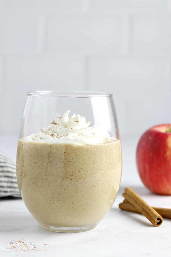 an apple pie smoothie in a glass, topped with whipped cream and cinnamon.