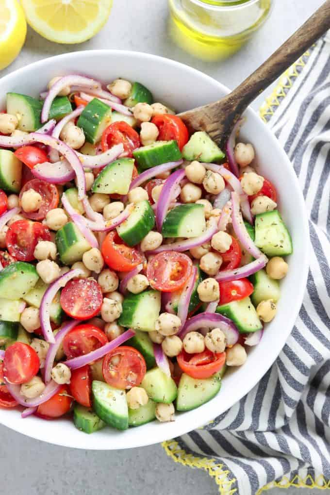Overhead view of tomato and cucumber salad in a white bowl with a wooden spoon inside. Lemon and oil on the side.
