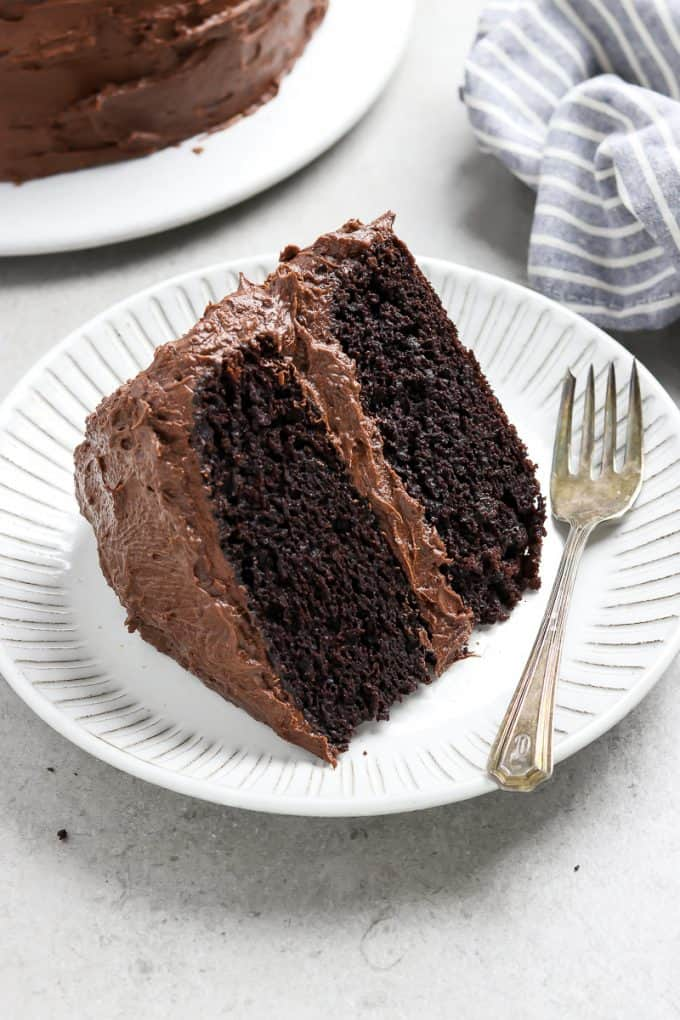 Side view of a piece of vegan chocolate cake on a white plate with a fork on the side.