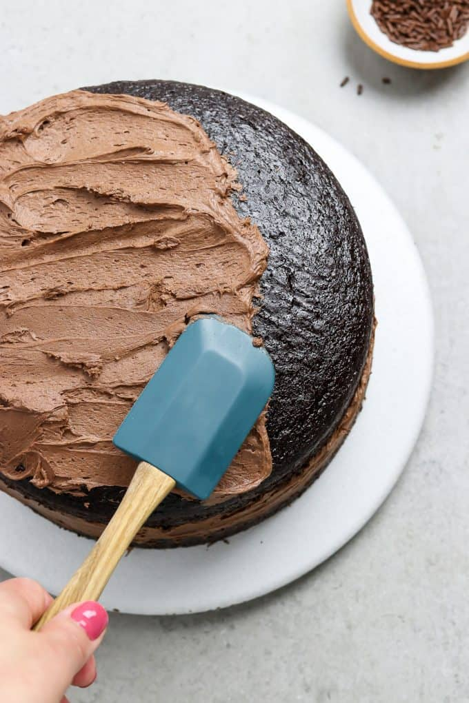 Frosting a cake with a blue spatula