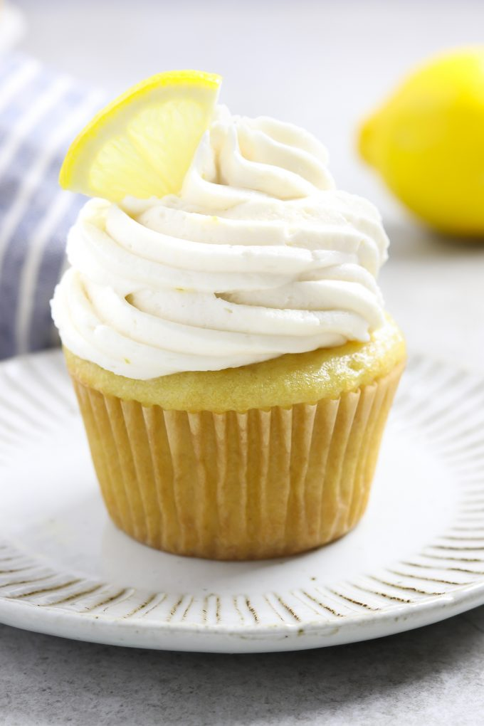Closeup view of a frosted cupcake on a plate. Fresh lemon in the background.