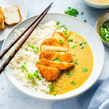 tofu katsu curry in a white bowl with chopsticks on top.