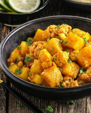 fully cooked aloo gobi in a black bowl. Soon on the side.