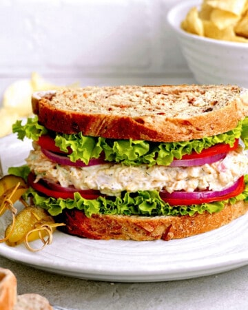 Front view of vegan tuna sandwich on a white plate with pickles on the side.