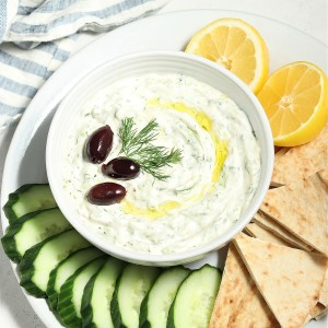 overhead view of tzatziki in a bowl with veggies and pita on the side.