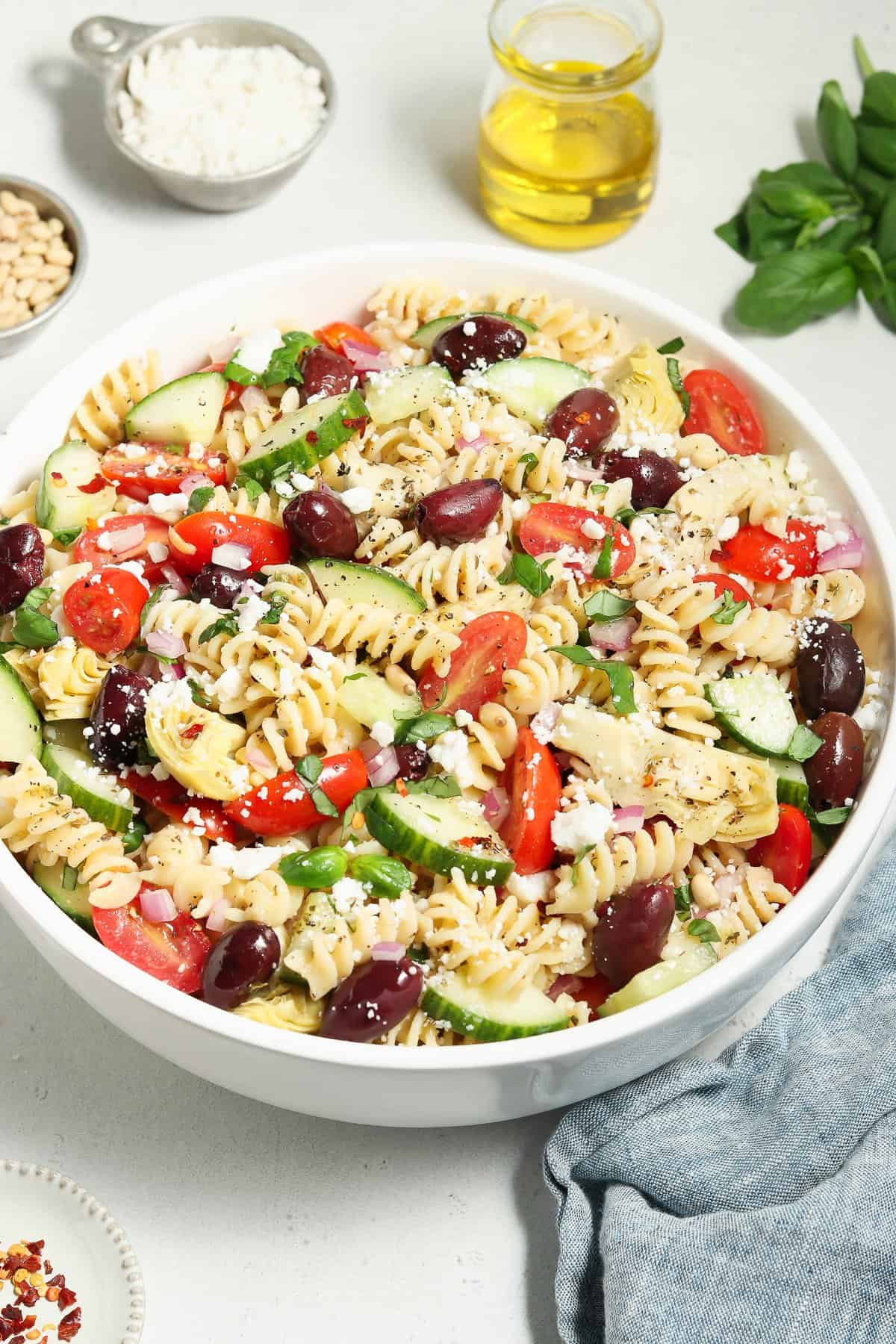 Tossed Mediterranean Pasta Salad in a large bowl. Olive oil, basil and pine nuts on the side.