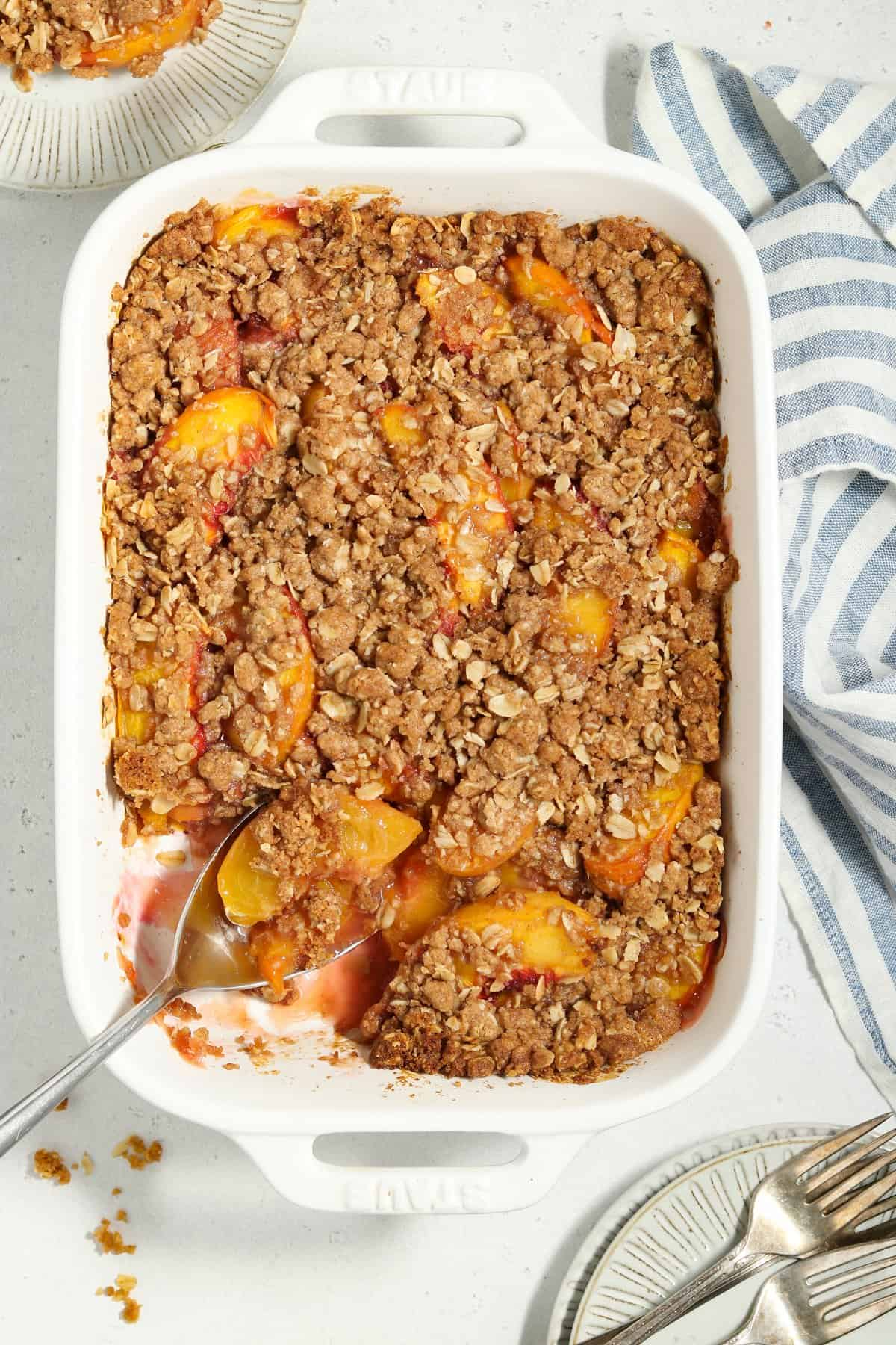 Overhead view of fully baked vegan peach crisp in a white casserole dish.
