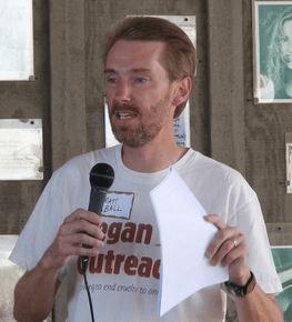 """kép leírása: fehér, cisznemű férfi, """"vegán tanácsadás"""" feliratú pólóban, mikrofonba beszél"""