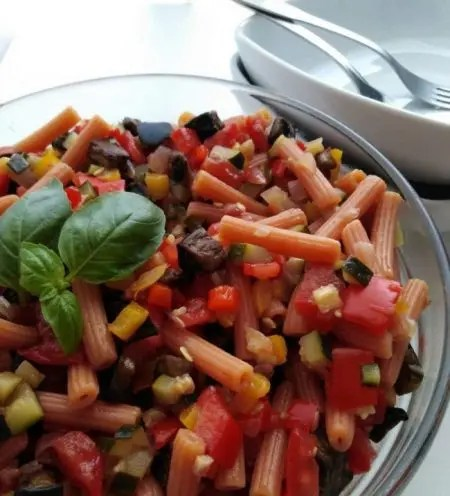 Italian Pasta Salad served in a bowl with plates in the background
