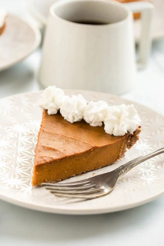 Close-up of vegan pumpkin pie with whipped cream decoration on the board
