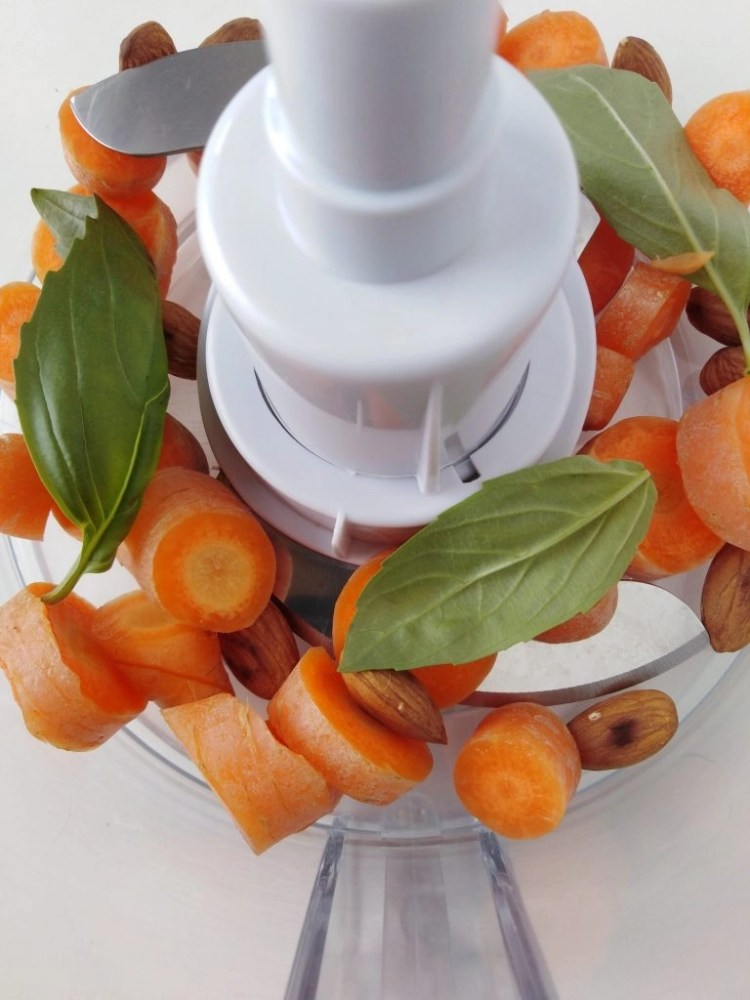 carrots, basil leaves and almonds inside a mixer