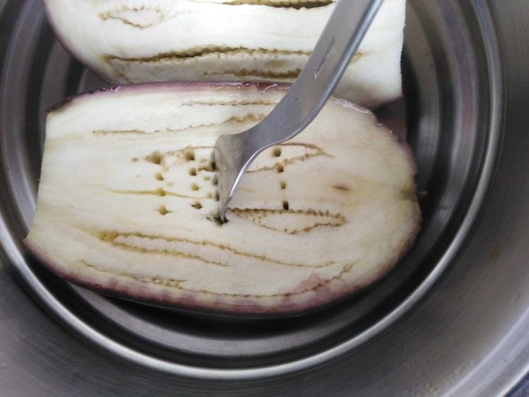 fork sticking in an eggplant inside a pan