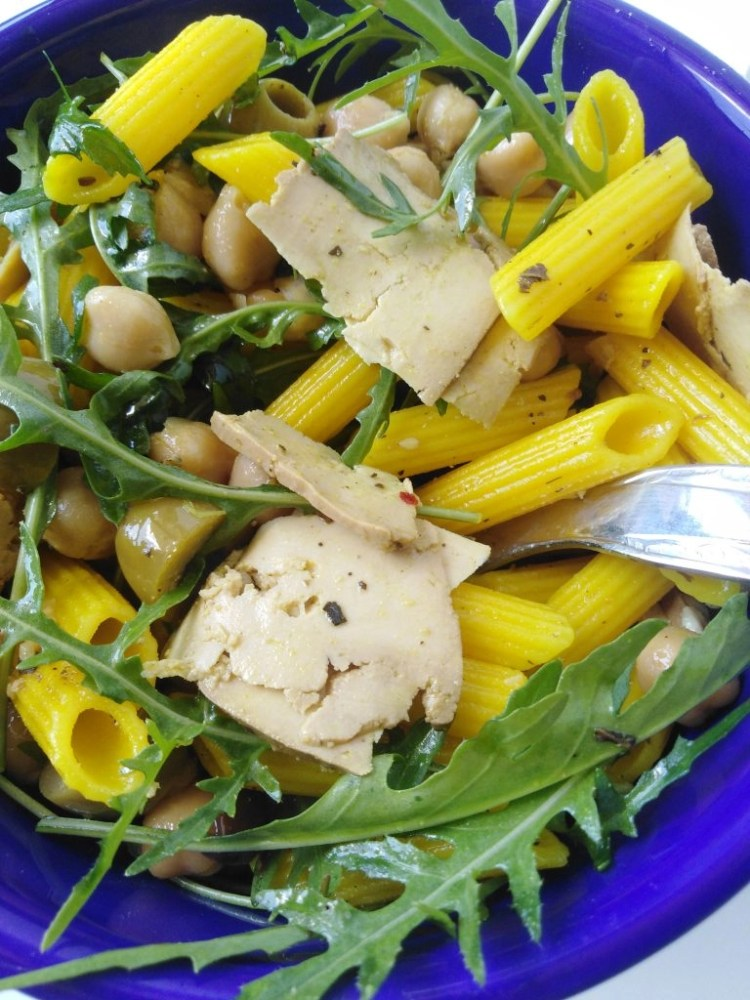 close-up from above of turmeric pasta with chickpeas in a blue bowl