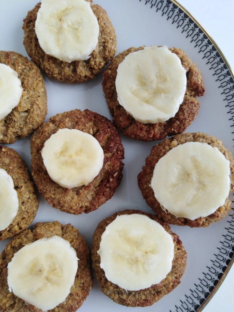 plate with vegan banana cookies with oat bran with sliced bananas on top