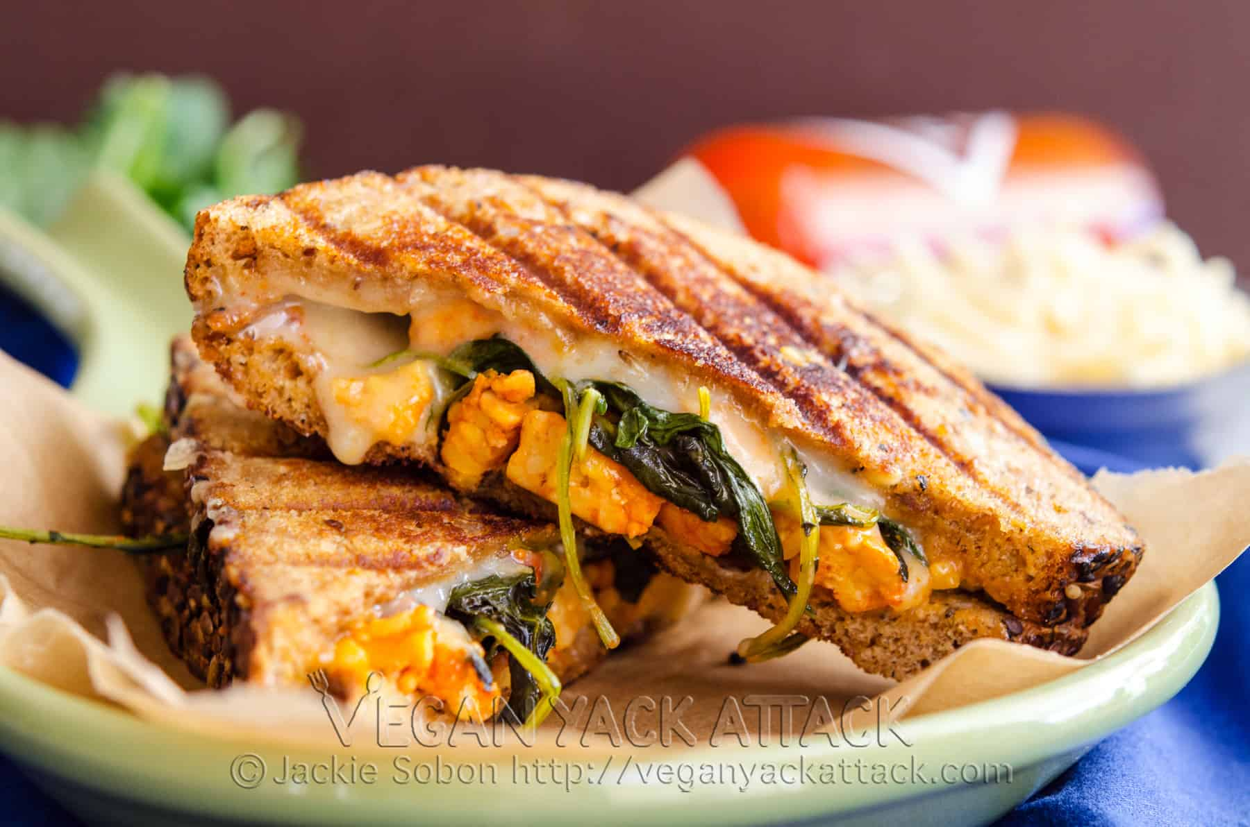 An nontraditional Grilled Buffalo Tempeh Mozzarella Sandwich, complete with spicy tempeh, kale, and melty vegan mozzarella.