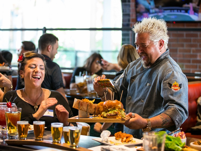 Guy Fieri assists a diner with her photo shot on the opening day of Guy Fieri's Vegas Kitchen & Bar at The Quad Resort & Casino on Thursday, April 17, 2014.