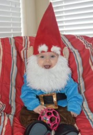 Baby smiling in a gnome Halloween costume