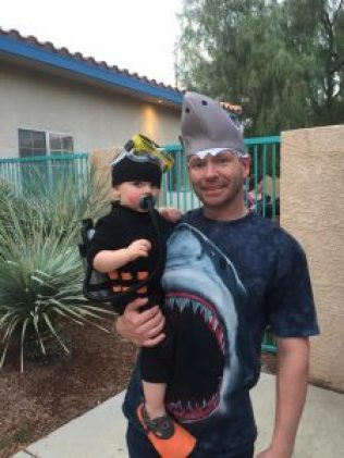 Baby boy dressed as a scuba diver with dad as a shark