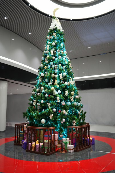 Huge decorated Christmas Tree with presents around inside a mall.