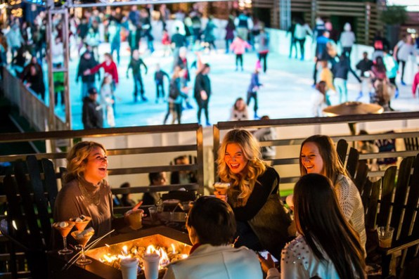 The Ice Rink at the Cosmopolitan, holiday event with skaters on ice and fire pit