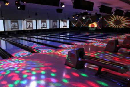 StrikeZone fun bowling, dark lanes with lights lit up all over-cosmic bowling