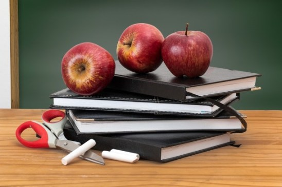Books, scissors, apples on a desk, back to school time