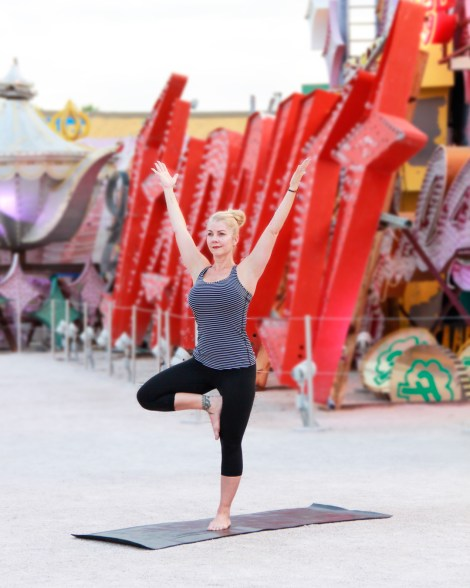 Hot Yoga at Neon Museum-instructor in yoga pose in front of neon sign.