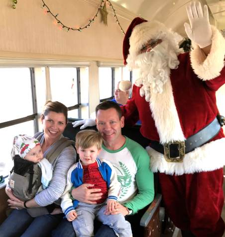 Santa in train car with smiling family, mom, daddy, toddler and baby