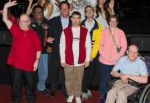 Easter Seals Nevada President and CEO Brian Patchett (center) poses with acrobatic performers of Mannheim Steamroller Christmas Las Vegas by Chip Davis and a group of Easter Seals Nevada clients.