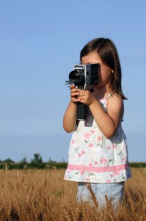 Girl holding a movie camera - stock image to accompany movie review