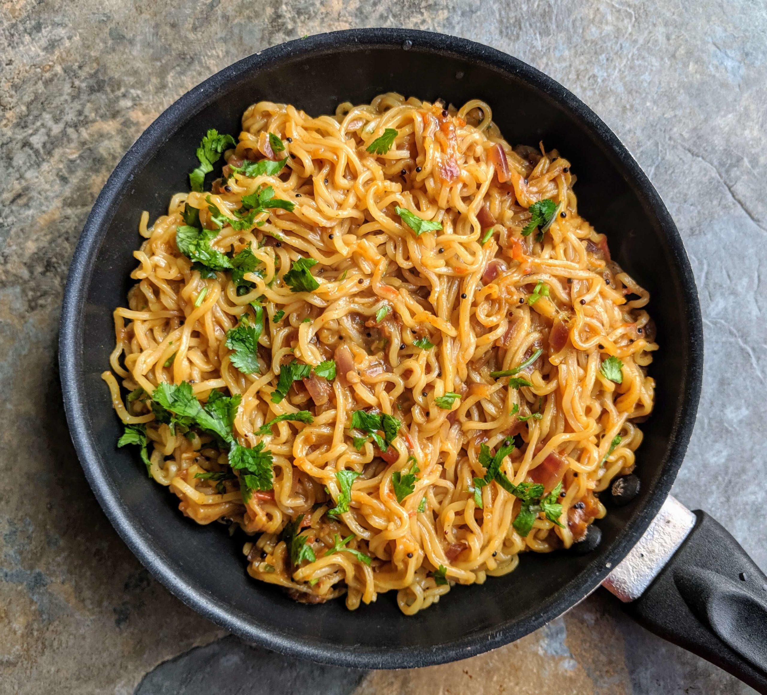 Street style maggi noodles are a spicy snack made by tossing maggi noodles in an onion tomato masala along with some spices.