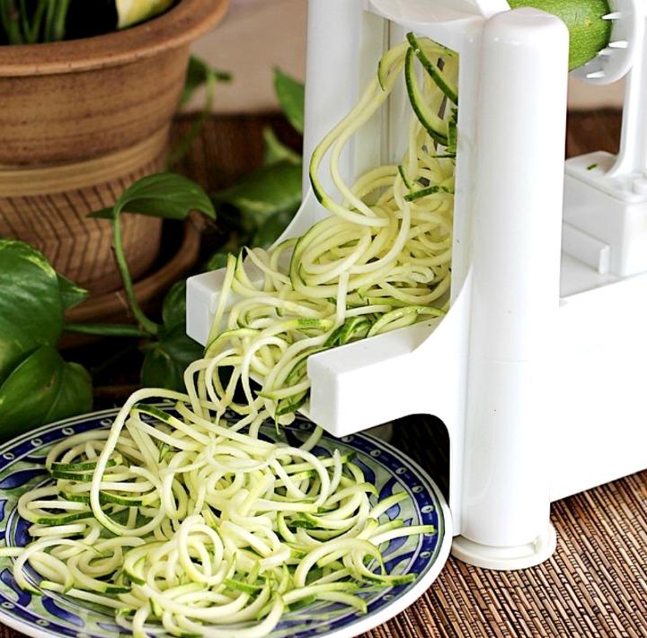 White plastic spiralizer machine making long strands of zucchini noodles