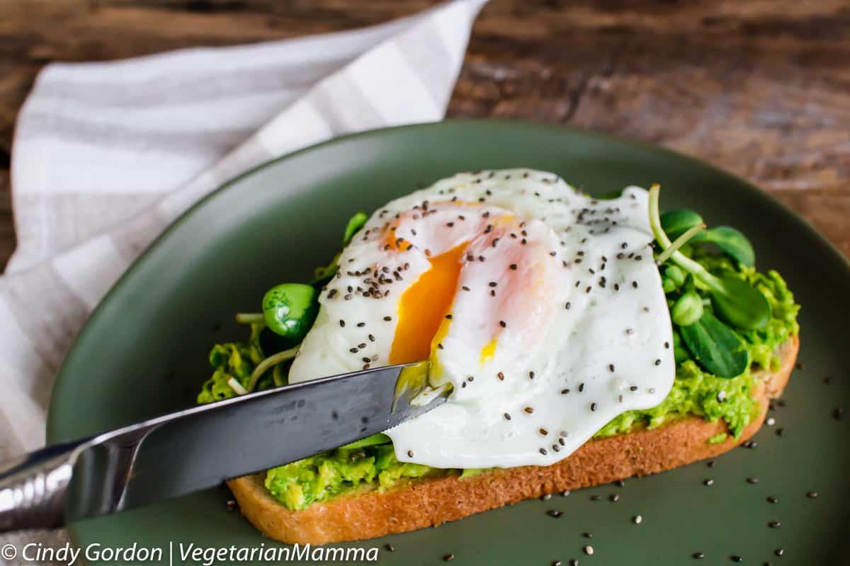 Knife cutting into fried egg avocado toast
