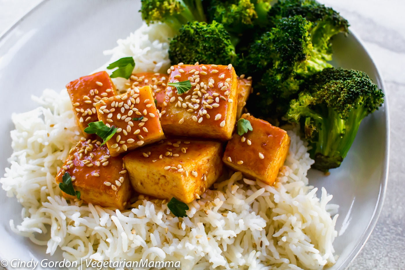 Honey Sriracha Tofu served with rice and broccoli on a white plate