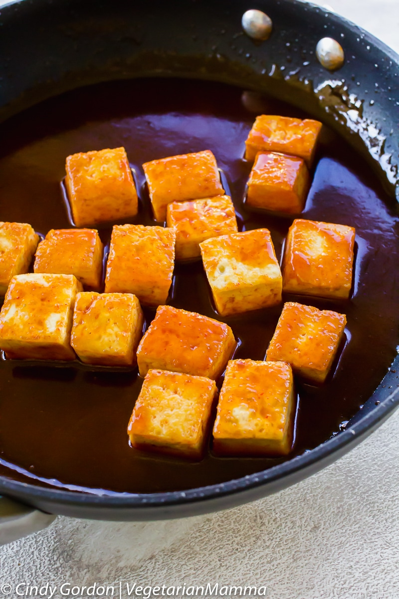 tofu cubes in sauce in a frying pan.