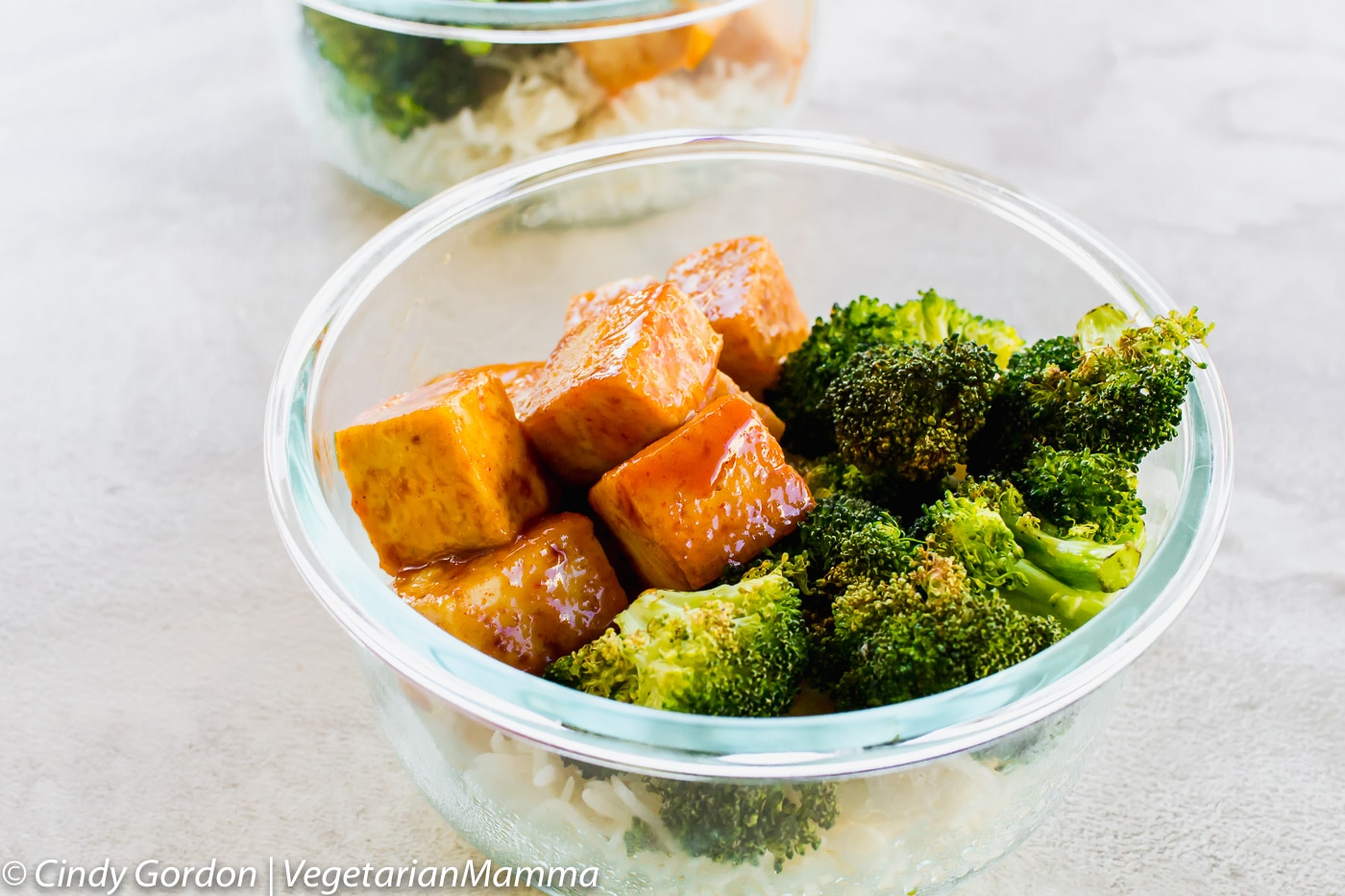 small glass bowl full of rice, broccoli, and tofu cubes.