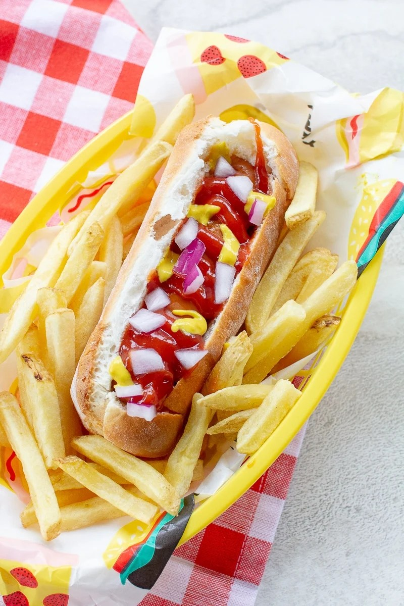 vertical picture of air fryer hot dogs in bun with fixings
