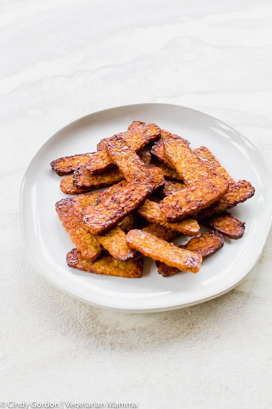 tall vertical picture of vegan bacon air fryer bacon on a white plate