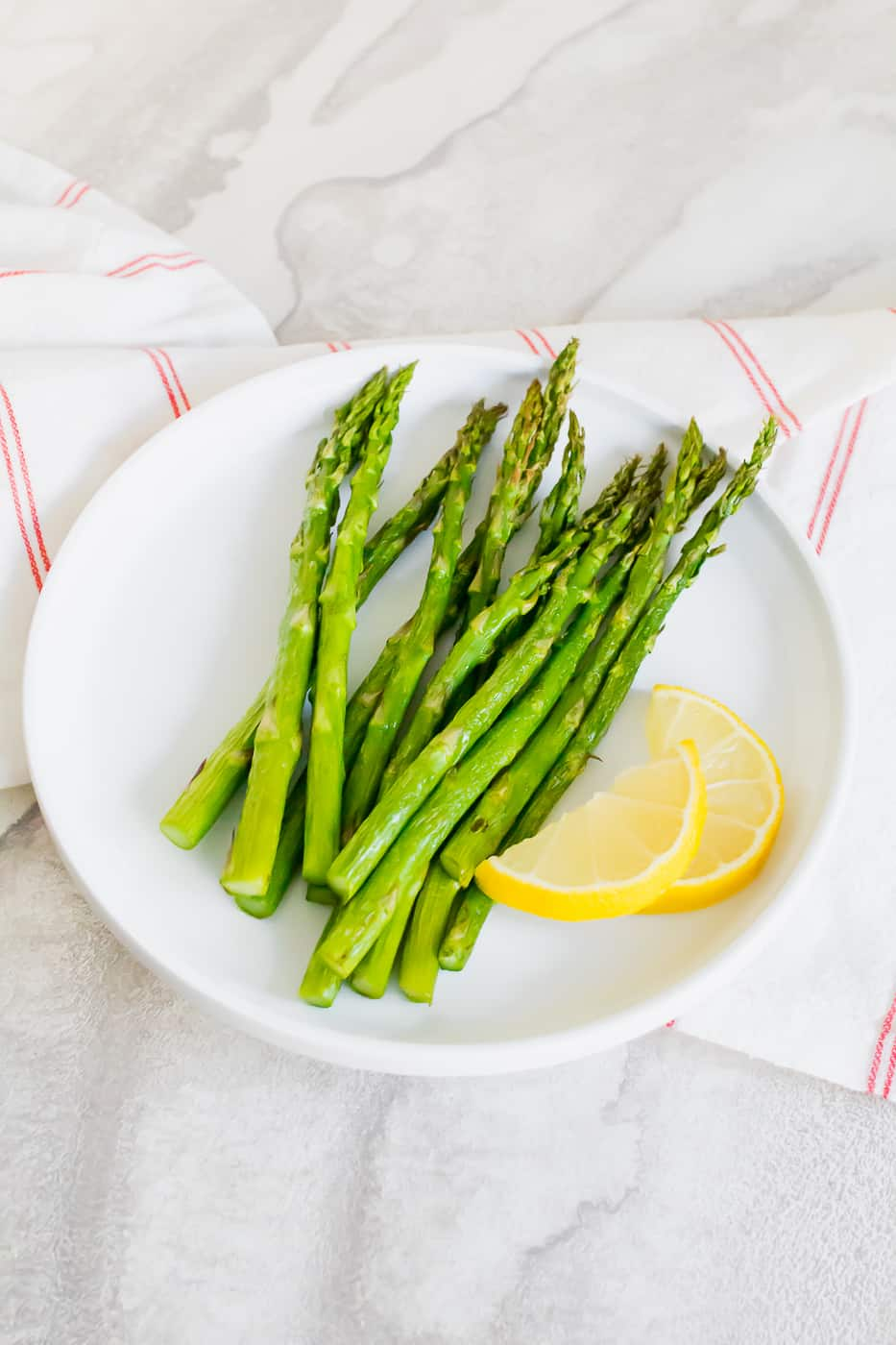 asparagus on a white plate with a yellow lemon cut in half