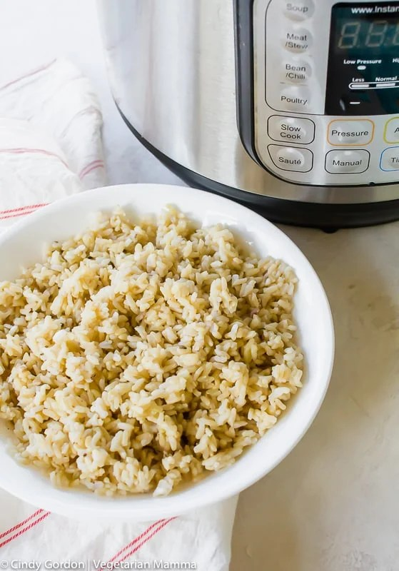 An overhead view of cooked rice beside an instant pot