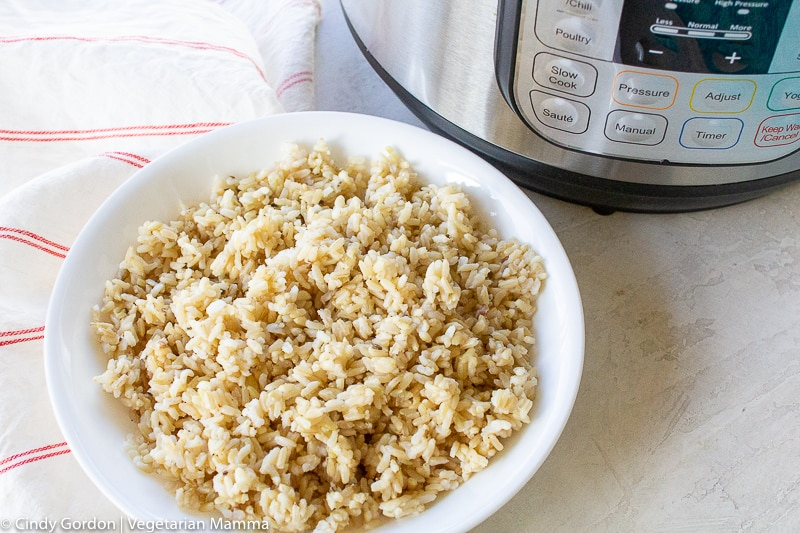 a white bowl filled with brown rice beside an instant pot