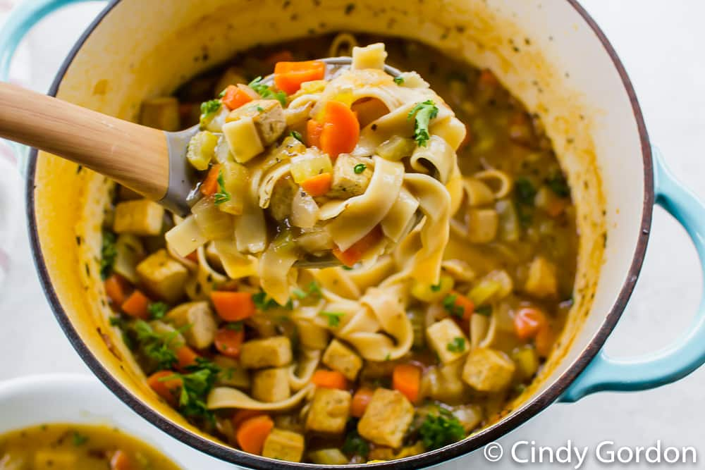 a ladle scooping a serving of soup with noodles and vegetables out of a pot of soup