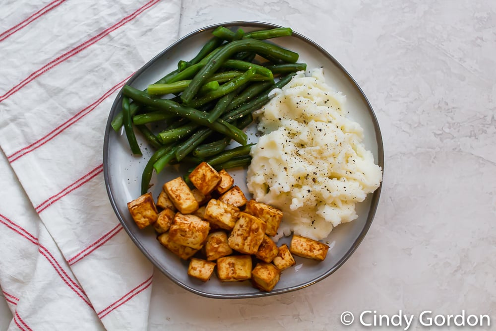 tofu squares with mashed potatoes and green beans on a round gray plate