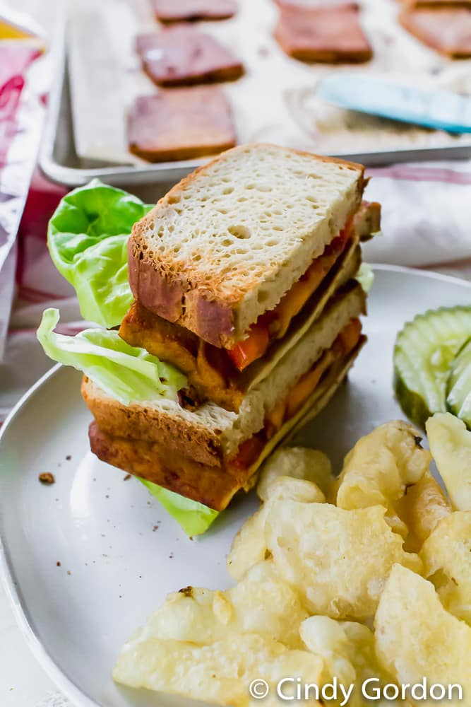 tofu bacon, tomato, and lettuce on toasted bread with a side of chips and pickles