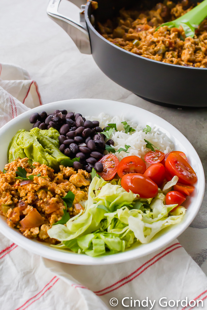 sofritas, lettuce, tomatoes, rice, black beans, and guacamole in a white bowl on a red and white towel.